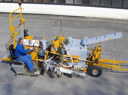 H18 con Extrusor MultiDotLine<sup>®</sup> utilizable en ambos lados y de fácil modificación, depósito 300 l, compresor rotativo y visor delizable hidraulicamente así como tubo de carga calentado, asientos en ambos lados junto de la máquina